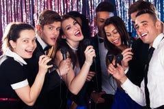 Amigos que cantan en los micrófonos en el partido del Karaoke imagenes de archivo