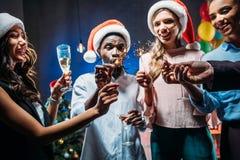 Amigos que celebran Año Nuevo con las bengalas Fotografía de archivo