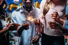 Amigos que celebran Año Nuevo con las bengalas Fotos de archivo