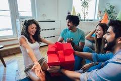 Amigos que celebran cumplea?os y que dan el regalo a una muchacha imágenes de archivo libres de regalías
