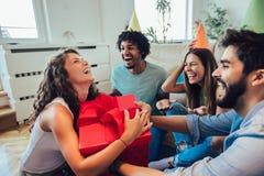 Amigos que celebran cumplea?os y que dan el regalo a una muchacha fotografía de archivo libre de regalías