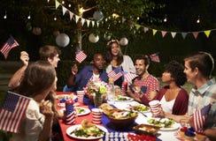 Amigos que celebran el 4to del día de fiesta de julio con el partido del patio trasero Foto de archivo libre de regalías