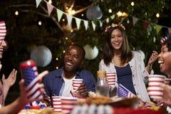 Amigos que celebran el 4to del día de fiesta de julio con el partido del patio trasero Fotos de archivo