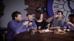 Amigos que celebran la fiesta de cumpleaños en los vidrios que tintinean del restaurante con el vino rojo con uno a Grupo de pers metrajes
