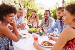 Amigos que cenan junto en una tabla en un jardín Fotografía de archivo libre de regalías