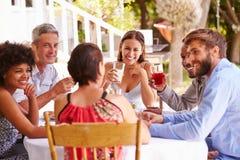 Amigos que cenan junto en una tabla en un jardín Foto de archivo