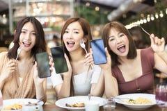 amigos que cenan y que muestran el tel?fono elegante en restaurante foto de archivo