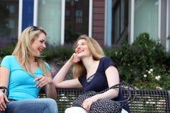 Amigos que charlan en un banco del jardín Imagenes de archivo