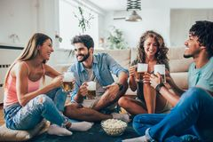 Amigos que comem a pipoca e que bebem a caneca de cerveja em casa, tendo o divertimento imagem de stock royalty free