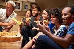 Amigos que comem a pizza em uma festa em casa, televisão de observação fotografia de stock