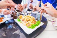Amigos que comem a salada fritada do camarão junto Foto de Stock