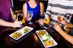 Amigos que comem um aperitivo com vinho fotos de stock royalty free