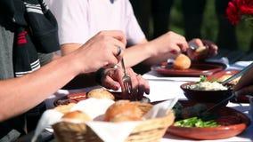 Amigos que comen el almuerzo en un día de verano hermoso almacen de metraje de vídeo