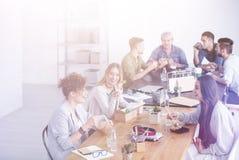 Amigos que comen en el escritorio imagen de archivo libre de regalías