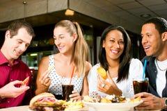 Amigos que comen la hamburguesa y que beben soda Foto de archivo libre de regalías