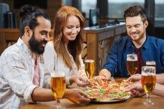 Amigos que comen la pizza con la cerveza en el restaurante Foto de archivo libre de regalías