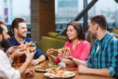 Amigos que comen la pizza con la cerveza en el restaurante Fotografía de archivo libre de regalías