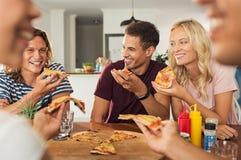 Amigos que comen la pizza en el país imágenes de archivo libres de regalías