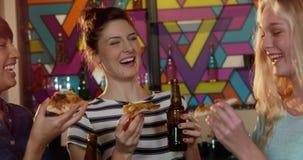 Amigos que comen la pizza mientras que comiendo cerveza