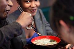 Amigos que comen la sopa de fideos en restaurante japonés Fotografía de archivo
