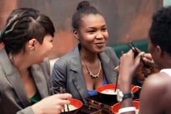 Amigos que comen la sopa de fideos en restaurante japonés Imagenes de archivo