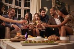 Amigos que comen los bocados como celebran en el partido juntos imagenes de archivo