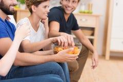 Amigos que comen los bocados mientras que mira la televisión Fotografía de archivo libre de regalías