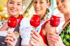 Amigos que comen manzanas de caramelo en Oktoberfest Imagenes de archivo