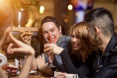 Amigos que comen un café junto mujeres y hombre en el café, hablando, riendo fotos de archivo
