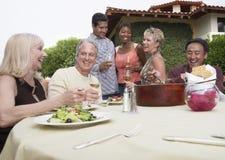 Amigos que comen y que beben en jardín Imagen de archivo libre de regalías