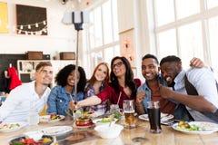 Amigos que comen y que toman el selfie en el restaurante fotografía de archivo libre de regalías