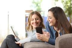 Amigos que comparten el contenido en línea con los dispositivos múltiples fotos de archivo