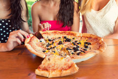 Amigos que comparten una pizza Imagen de archivo libre de regalías