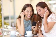Amigos que comparten y que escuchan la música con smartphone Imágenes de archivo libres de regalías