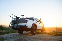 Amigos que conduzem o caminhão Offroad do recolhimento nas montanhas com as bicicletas no corpo no por do sol Conceito da aventur fotos de stock