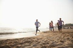 Amigos que correm na praia e que têm o divertimento Fotos de Stock