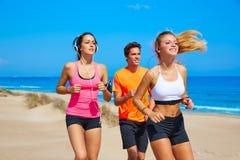 Amigos que correm na praia feliz no verão fotos de stock royalty free