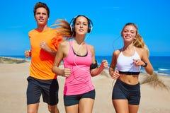 Amigos que correm na praia feliz no verão imagens de stock royalty free