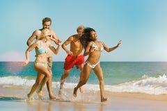 Amigos que corren el vacaciones de la playa imagen de archivo libre de regalías