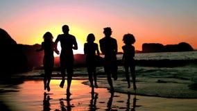 Amigos que corren en el mar bajo oscuridad