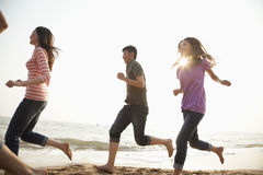 Amigos que corren en la playa y que se divierten Imagen de archivo