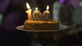 Amigos que dan a la mujer mayor sonriente de la torta de cumpleaños, celebración de 100 aniversarios metrajes