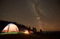 Amigos que descansam ao lado do acampamento, fogueira sob o céu estrelado da noite fotografia de stock