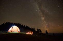 Amigos que descansan al lado del campo, hoguera debajo del cielo estrellado de la noche imagenes de archivo