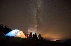 Amigos que descansan al lado del campo, hoguera debajo del cielo estrellado de la noche foto de archivo libre de regalías