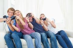 Amigos que disfrutan de los juegos video foto de archivo