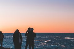 Amigos que disfrutan de una puesta del sol por el mar fotografía de archivo libre de regalías