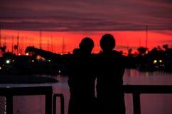 Amigos que disfrutan de una visión escénica en la puesta del sol Fotografía de archivo libre de regalías