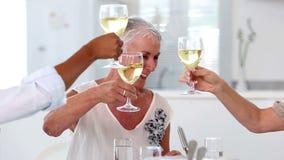 Amigos que disfrutan del almuerzo junto y que aumentan sus vidrios metrajes