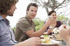 Amigos que disfrutan del partido de cena al aire libre Foto de archivo